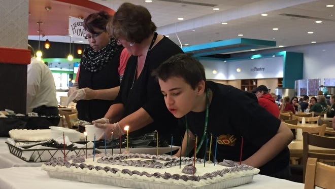 Zach Foller, a boy with autism from Dover, blows out the candles at his surprise 13th birthday party at York College. The York College chapter of Best Buddies threw him a party after finding out no one came to his birthday party two years ago.