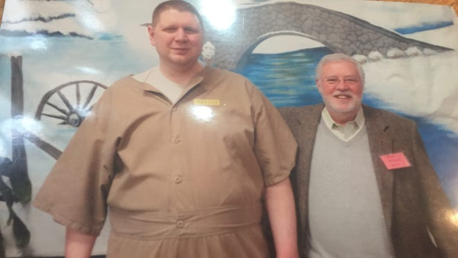 Andrew Royer poses with an attorney at the Pendleton Correctional Facility in Pendleton, Ind.