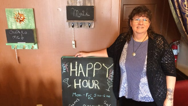Owner Pam Garbisch stands next to a happy hour sign at Gypsie Gems, 111 W. Second St. in downtown Marshfield.