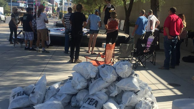 """Supporters of defendants in the Bundy Ranch standoff trial stand outside U.S. District Court in Las Vegas on Aug. 14, 2017. The supporters piled up """"tea bags"""" as a reminder of liberty."""