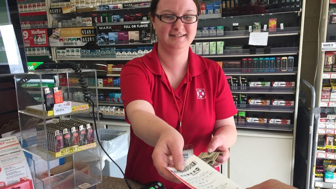 Aliza Armentrout, a sales associate at Circle K on West State Street, sells a Powerball ticket Tuesday to a customer. The multi-state Powerball jackpot has risen to an estimated $700 million ahead of Wednesday night's drawing.