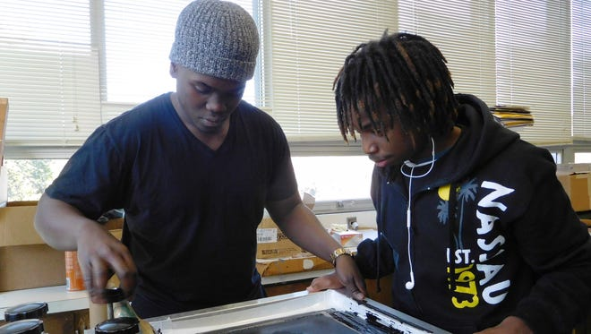 Hosea Washington Jr. and Quincy Cameron make tiny adjustments for perfect registration of the print at Rickards High School.