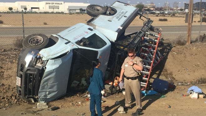A witness talks to a CHP officer about how another motorist merged in front of this truck causing the driver to swerve off the roadway.