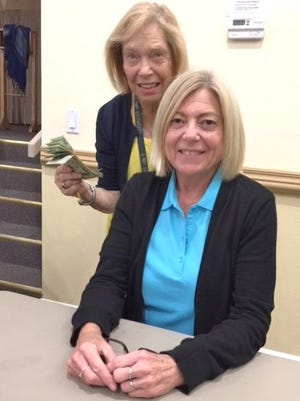Bingo Chair Sue Baum presents Marco Island resident Deb Rubenzer with her big winnings at JCMI's Monday Night Bingo.