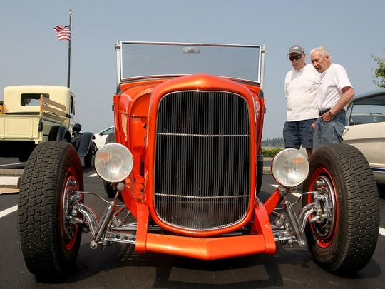 Saints Car Club members Pudge Wiley and Johnny Winters, both of Port Orchard, look over a 1932 Ford deuce roadster during the Cruz preview on Friday. The 30th annual Cruz is scheduled for 10 a.m. to 4 p.m. Sunday on the Port Orchard waterfront.