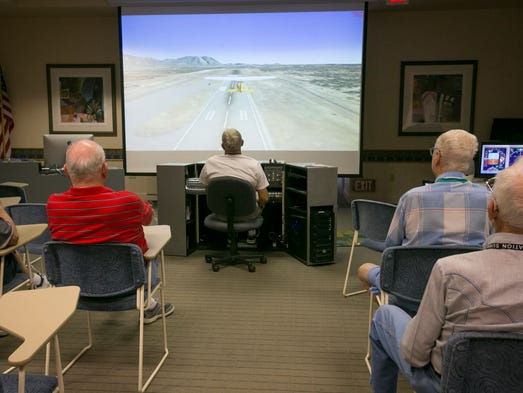 "As one man ""pilots"" the flight simulator, other members of the Computers West PC Group watch during a class at the Palm Ridge Recreation Center in Sun City West."