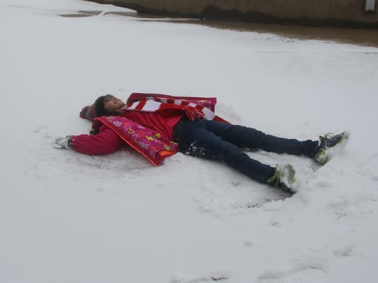 Bella Martinez, 10, made her very first snow-angel on Friday at the Living Desert Zoo.