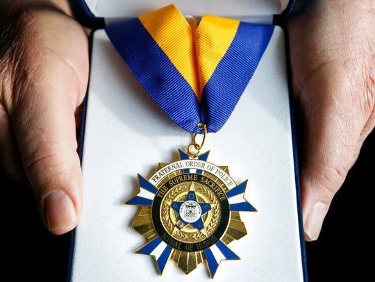 Gary Fredinburg holds the Medal of Honor presented