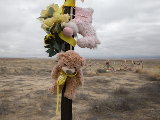 A teddy bear hangs on a sign post near a makeshift