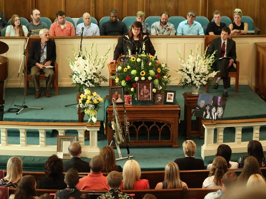 Katie McGill spoke briefly about her father, Chuck McGill, Sunday at a memorial service that left an overflow crowd sitting in the choir loft and standing in the aisles.