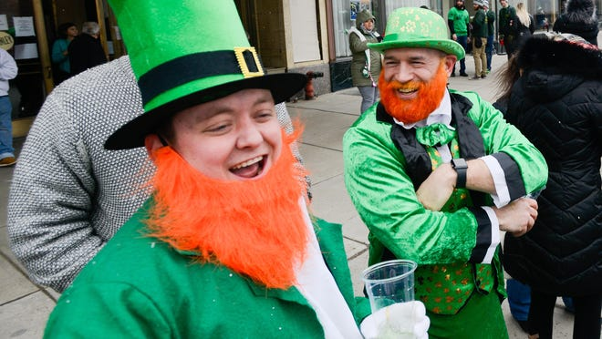 Dressed as leprechauns, James Meyers and Mike Amante smile and cheer on parade members while attending the St. Patrick's Day Parade in 2019 along Genesee Street in Utica.