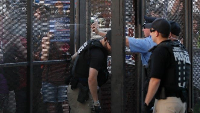 Police spray protesters through the fence near the AT&T Station in Philadelphia, Tuesday, July 26, 2016, during the second day of the Democratic National Convention. (AP Photo/Matt Slocum)