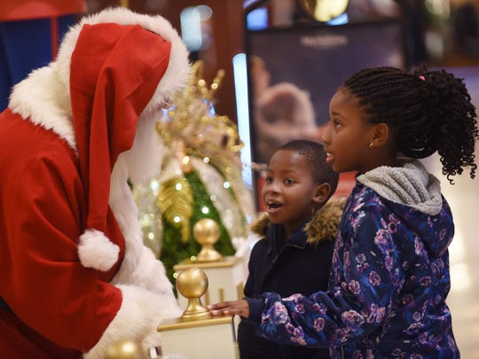 Annahbelle Jean (age 8) of Union and her brother Vinsaint (age 6) talk with Santa as they walk by at Bergen Town Center in Paramus on November 27th, 2017.