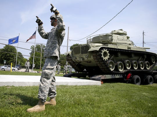 Derrick Voruda of the Wisconsin National Guard signals as an M60 battle tank is moved Friday from the back of a heavy equipment transport to a concrete pad in front of American Legion Post 33 in Neenah.
