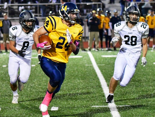 South Lyon's Will Kelley (with ball) is pursued by
