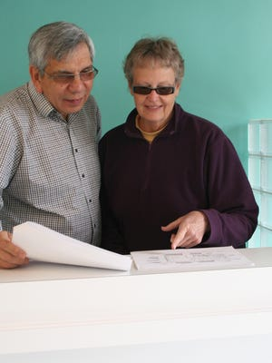 Chris Aquino, left, and Mary Dearhamer review plans for the Silco Theater Concession.