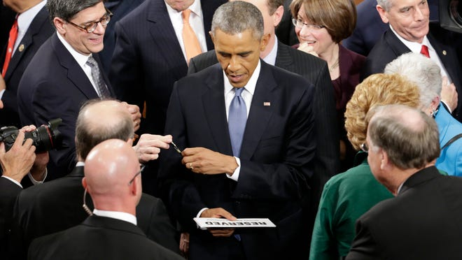 President Barack Obama prepares to sign an autograph on Capitol Hill in Washington, Tuesday, Jan. 20, 2015, after giving his State of the Union address before a joint session of Congress. (AP Photo/Pablo Martinez Monsivais)