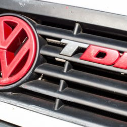 A red Volkswagen logo on a diesel-powered vehicle next to the abbreviation TDI (Turbocharged direct injection)