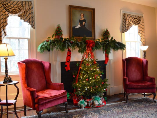 The library mantle features fragrant evergreens and two rosemary topiaries flanking the 1950s portrait of Hessie Morrah, Greenville's most renowned garden club leader.