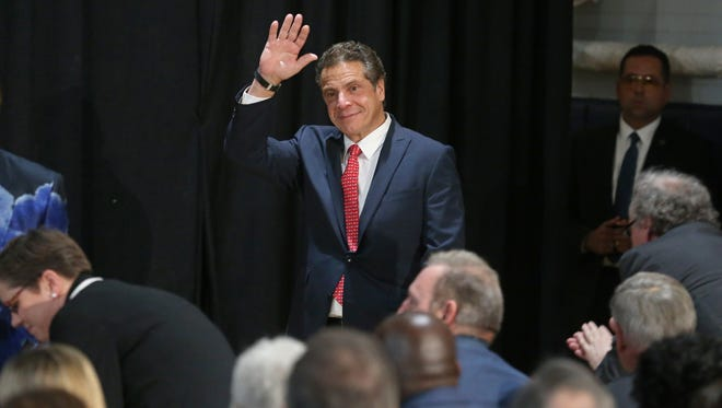 New York Governor Andrew Cuomo waves to a packed house as he arrives to talk about fighting poverty during his stop at the Community Place of Rochester Wednesday, Nov. 30, 2016. He has to decide whether to sign an indigent defense bill.