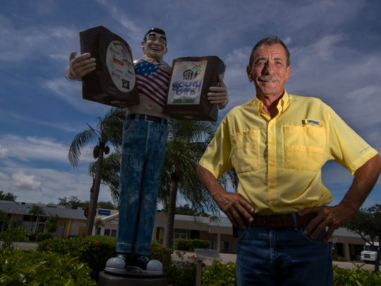 Elmer Tabor Jr. poses by the Big John statue in downtown