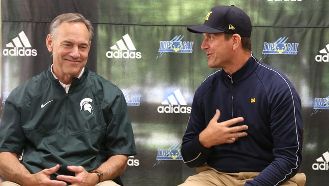 Michigan State Spartans head coach Mark Dantonio, left, and Michigan Wolverines head coach Jim Harbaugh talk to reporters during the Sound Mind Sound Body football camp held at Wayne State University on June 10, 2016.