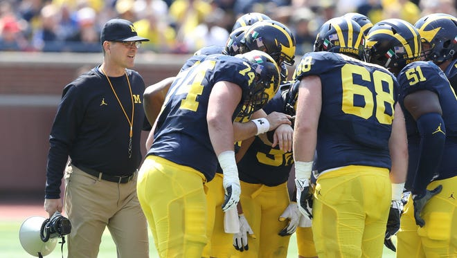 Michigan head coach Jim Harbaugh watches the offense huddle in the spring game Saturday, April 15, 2017 at Michigan Stadium in Ann Arbor.