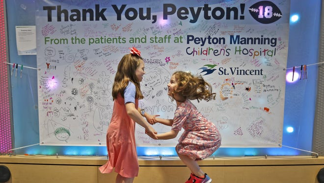 Sisters Ellie and Lilly Cooley jump on sensors that initiate sounds of nature in the lobby of the Peyton Manning Children's Hospital. The family met Manning through the hospital and have remained in touch ever since.