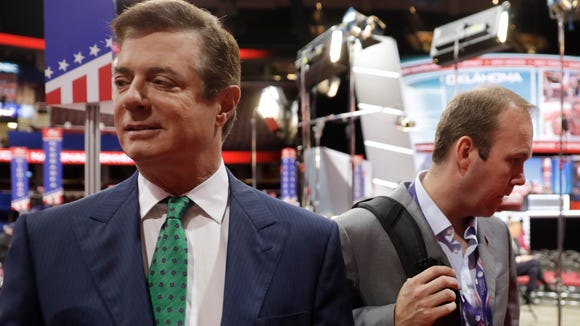Trump Campaign Chairman Paul Manafort talks to reporters on the floor of the Republican National Convention at Quicken Loans Arena in Cleveland as Rick Gates listens at back right on July 17, 2016.