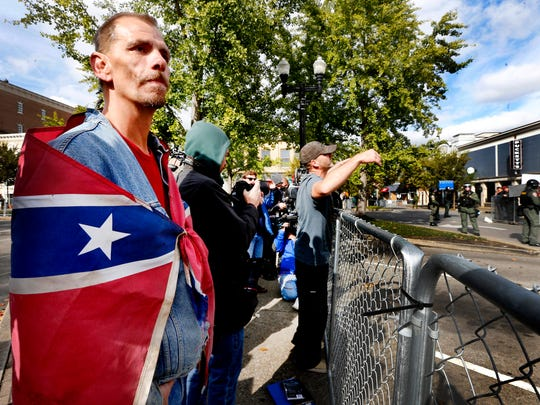 "Keith Fuller, 49, of Murfreesboro is wrapped in a Confederate flag as David Lee Oliphant, 37, of Portland yells across a police line to counter protesters during the ""White Lives Matter"" rally on the square in Murfreesboro, on Oct. 28, 2017. The Anti-Defamation League as tracked more than 100 incidences of white supremacist propaganda in Tennessee since the beginning of 2018."
