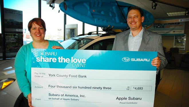 York County Food Bank's interim executive director Amy Chamberlin, left, accepts a $4,693 check from Apple Subaru General Manager Rob Dell, right.