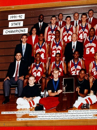 Robert Sanders looks at a photo of the 1992 Richmond High School State Championship team at the Tiernan Center on Monday Jan. 7, 2002. Sanders is third from the left in the third row, #30.