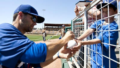 Jamey Carroll of the LA Dodgers signs a ball for Aidan Neill, 7, of Los Angeles, at the autograph signing along the baseline before the LA Dodgers vs. Chicago White Sox game on Sunday, March 13, 2011, at Camelback Ranch in Glendale.