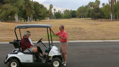 Charles Yoshioka, standing, talks with Dale Thune and Mary Wills in September at the Rancho Mirage Country Club about the closure of the golf course. The new owner has since put up a chain-link fence that officials say violates city codes.