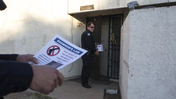 "Phoenix police officers go door to door passing out ""Shannon's Law"" fliers Dec. 30, 2015, at a Phoenix condo complex. Police are doing the same thing this year to raise awareness about the dangers of random gunfire."