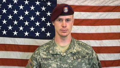 In this undated image provided by the U.S. Army, Sgt. Bowe Bergdahl poses in front of an American flag. U.S. officials say Bergdahl, the only American soldier held prisoner in Afghanistan, was exchanged for five Taliban commanders being held at Guantanamo Bay, Cuba, according to published reports.