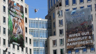 Greenpeace activists hang banners outside P&G , leading to vandalism and burglary charges.