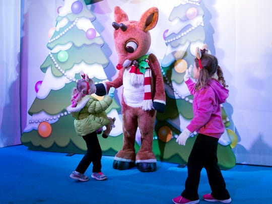 Paisley and Sadie Daniels meet Rudolph the Red-Nosed  Reindeer at Dollywood on Friday, December 2, 2016. The theme park was not damaged by nearby wildfires but more than a dozen of the resort's Smoky Mountain Cabins were destroyed or damaged.