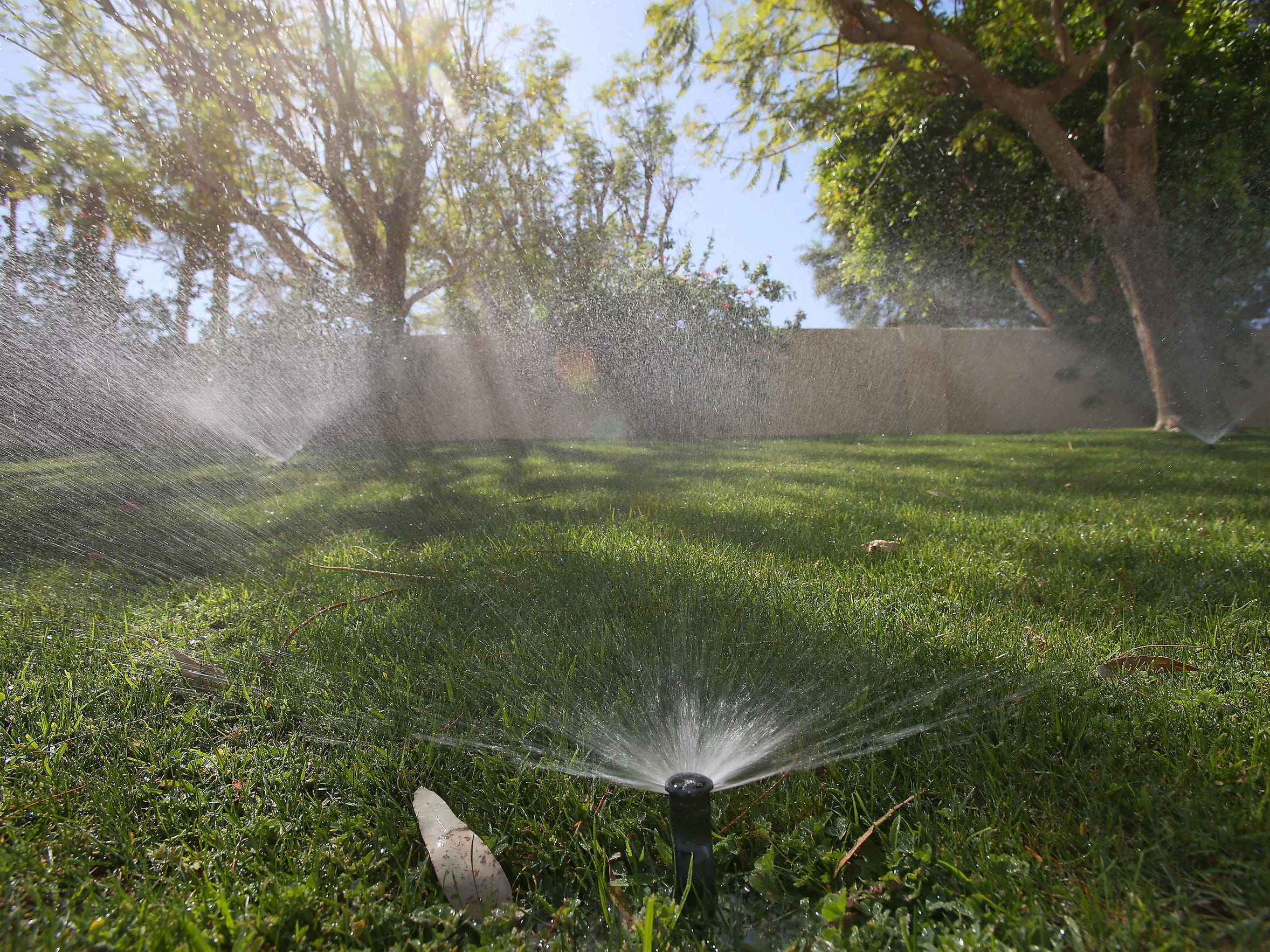 Sprinklers water a lawn at a home that is supplied