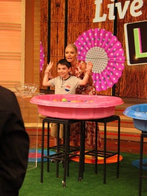 Tyler Carach, also known as Donut Boy, poses with television morning host Kelly Ripa during the Bratt, Florida boy's taping for a 'Live with Kelly and Ryan show in July. The episode will air on Monday, Sept. 4.