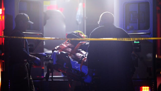 Emergency crews place the victim of a shooting in an ambulance Sunday night in Winton Hills. The 23-year-old man was shot multiple times in the legs.