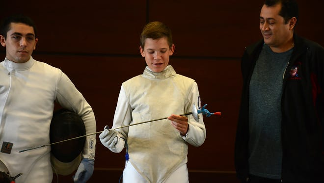 David Tierney, 14, explains how his fencing foil transmits electric signals to score a match.