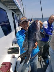 Todd Teadaguch holds a sea bass he landed on the Dauntless