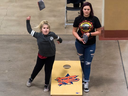 Addison Renegar, left, and Sidney Fiveash pass the time playing cornhole while attending the American Cornhole Organization's Majors tournament at the Jacob Building on Saturday, December 16, 2017.