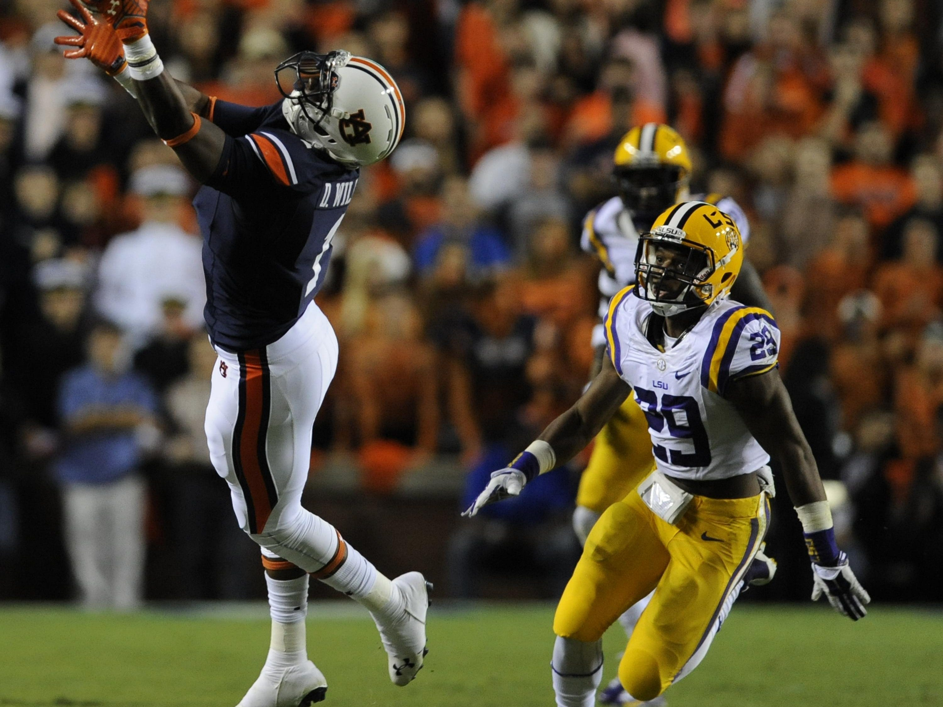 Auburn wide receiver D'haquille Williams hauls in a long reception against LSU safety Rickey Jefferson at Jordan-Hare Stadium on Oct. 4, 2014.