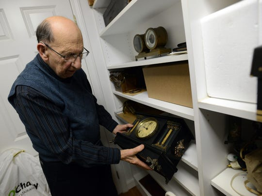 Joe Clark pulls a mantel clock from a shelf in his home Tuesday in Canal Winchester. Clark taught himself to fix clocks in the early 1980s and has been repairing and selling clocks since then.