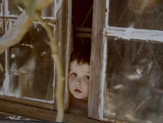 1-year-old Silas peers from a window of the original