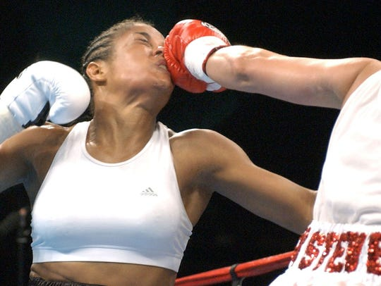 IBA super middleweight champion Laila Ali, left, takes an early second-round jab to the face Saturday, Aug. 23, 2003, from challenger Christy Martin. Muhammad Ali's daughter showed little wear from the jab as Ali hammered Martin for three rounds before finally finishing her off 48 seconds into the fourth round.