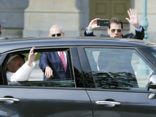 Pope Francis waves from his Fiat 500L as he leaves Capitol Hill in Washington, Thursday, Sept. 24, 2015, following his address to a joint meeting of Congress. (AP Photo/Steve Helber)
