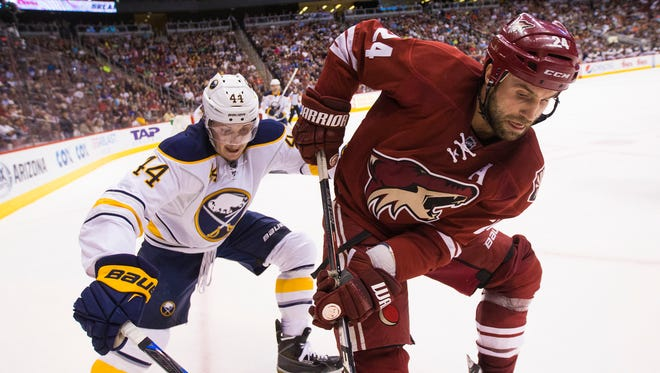Arizona Coyotes center Kyle Chipchura is pressured by Buffalo Sabres forward Nicolas Deslauriers during the second period at Gila River Arena in Glendale on March 30, 2015.